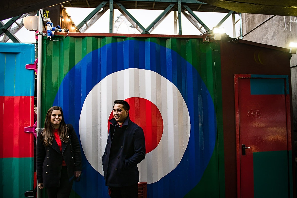 Fashionable couple stand in front of street art in London