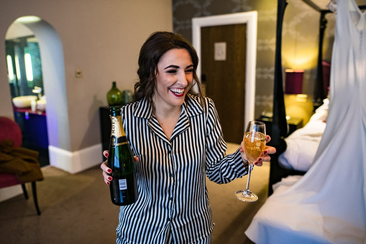 bridesmaid has a drink of champagne before wedding