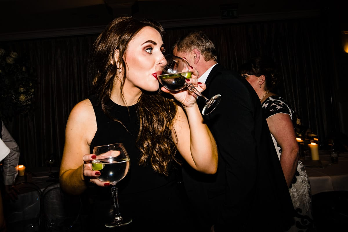 wedding guest carries two drinks on dance floor candid
