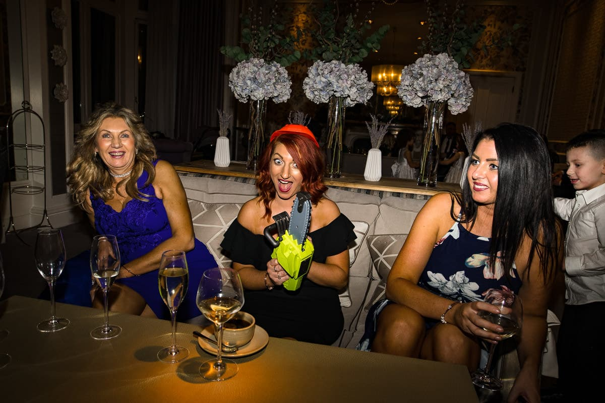 wedding guests drink and joke with toy chainsaw