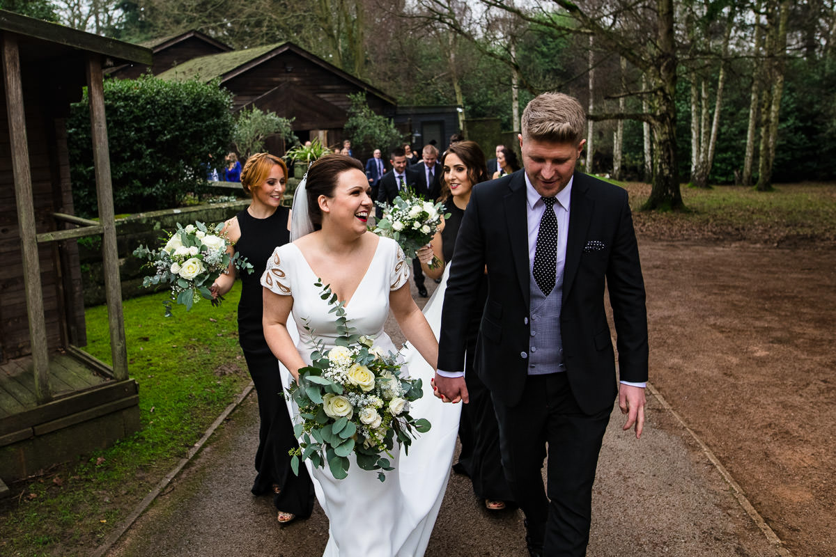 wedding party follows bride and groom as they leave hampton manor ceremony