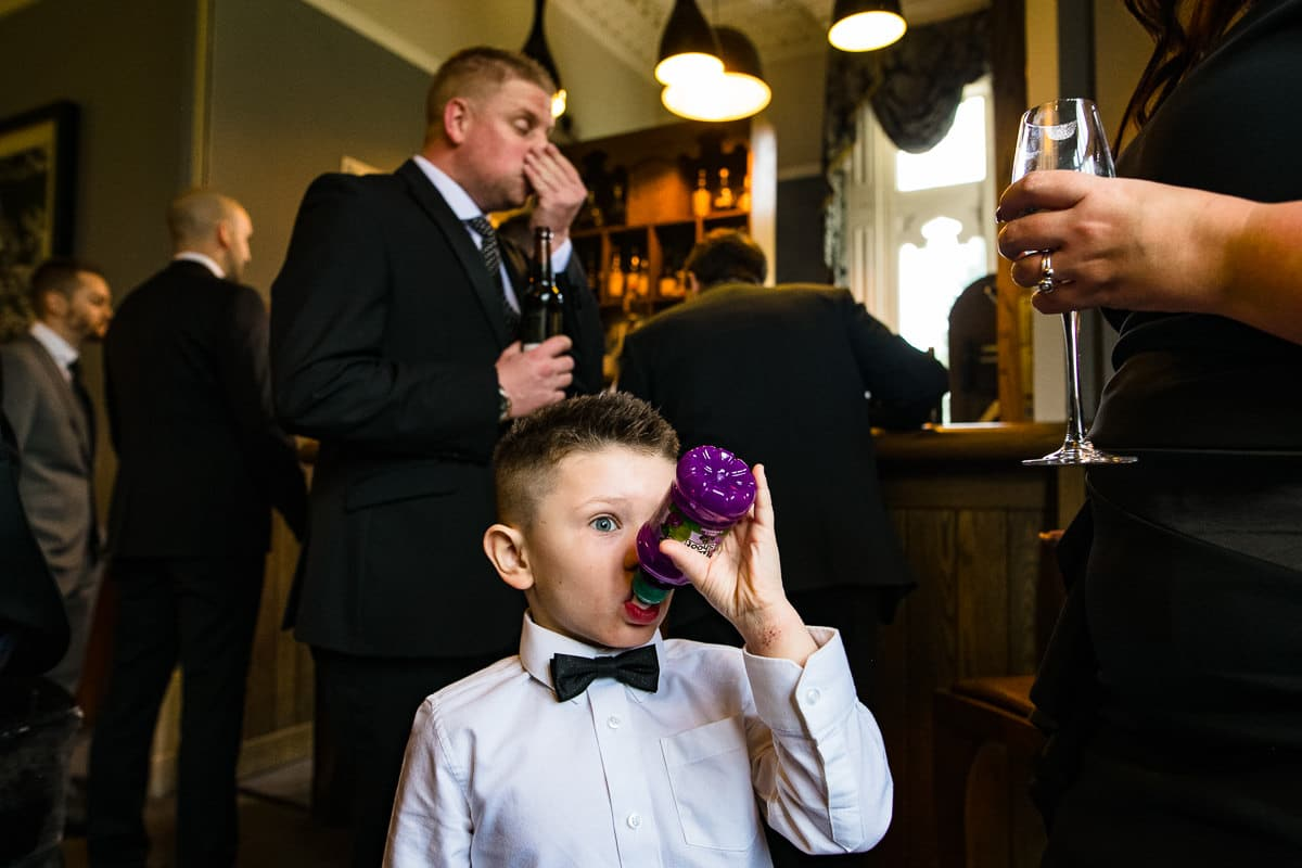 young wedding guest sips on juice bowtie