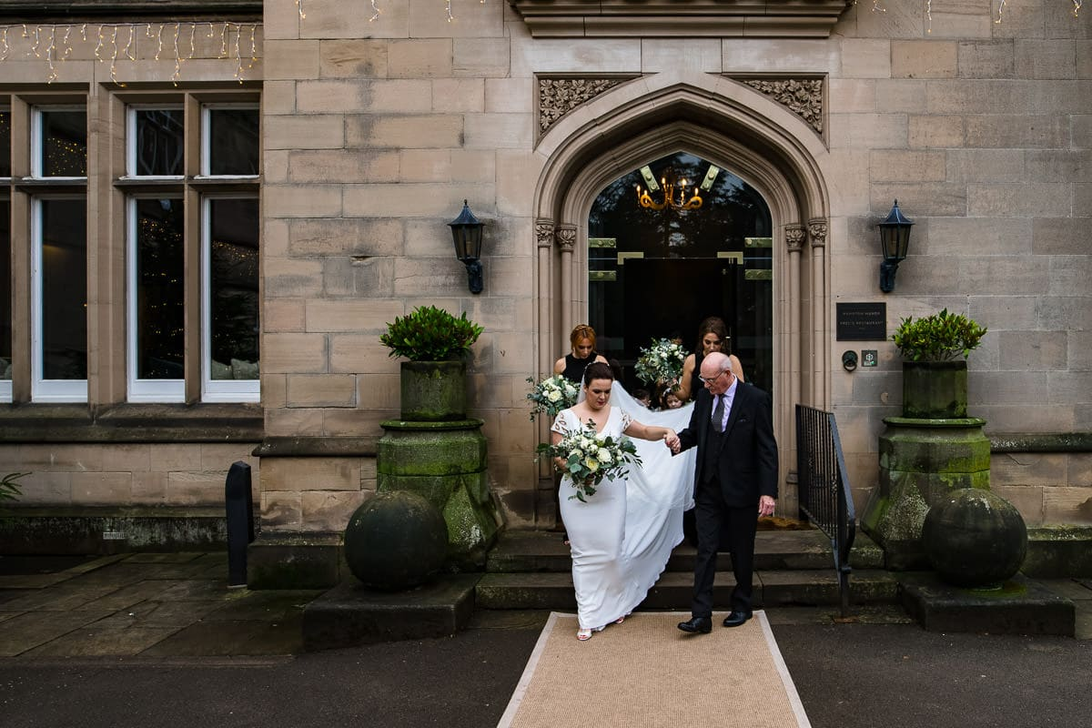 wedding guests assist bride as she leaves wedding location