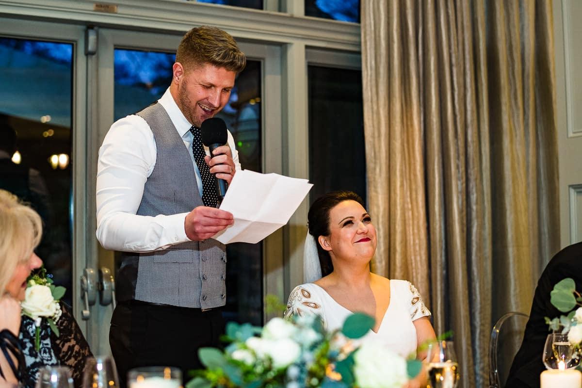 bride smiles at grooms wedding speech Hampton manor