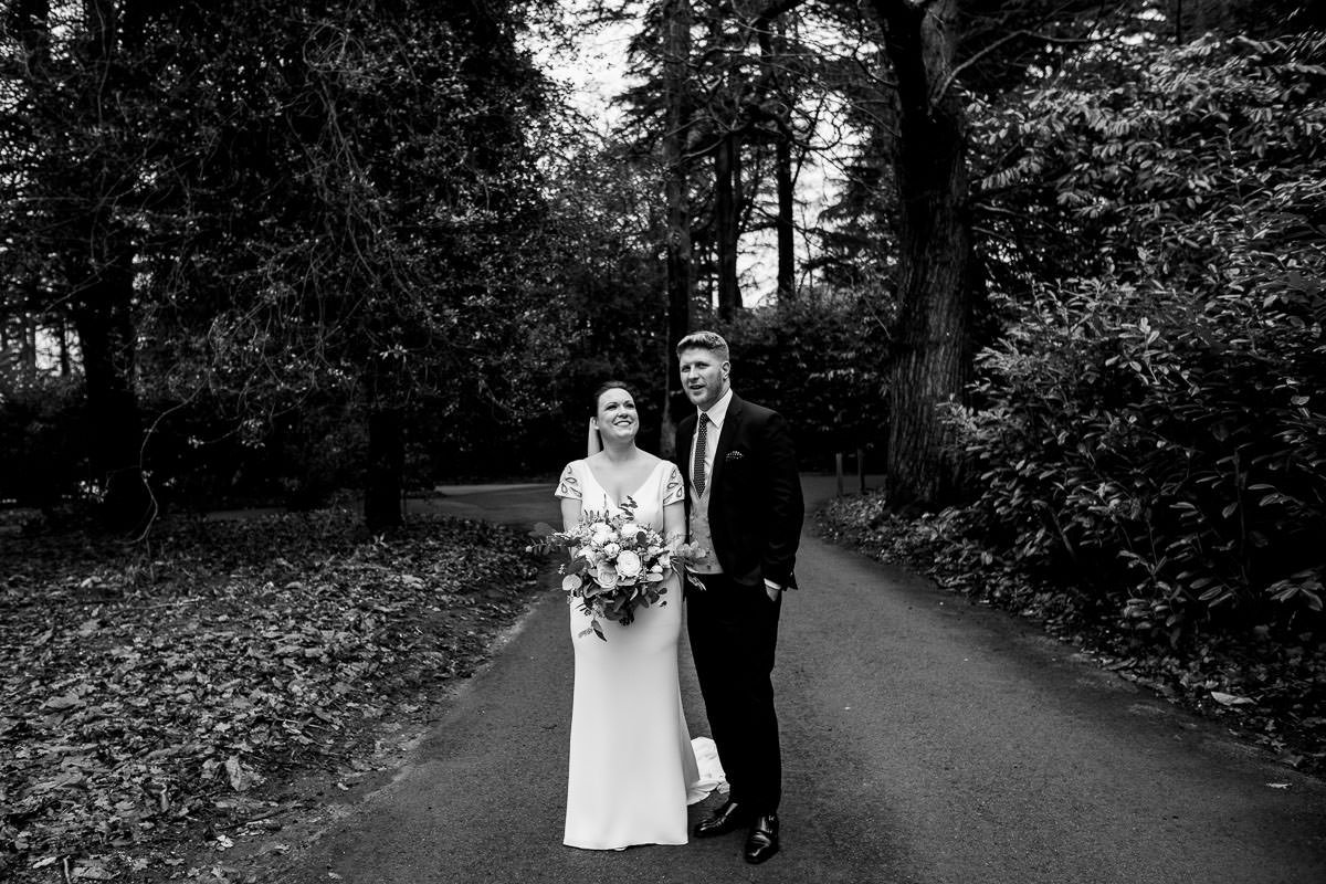 bride and groom take stroll through winter woodland
