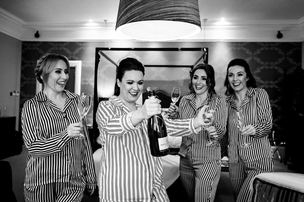 bride opens champagne bottle Hampton manor wedding