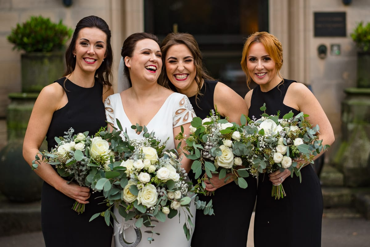 bride and bridesmaids laugh and embrace for photo