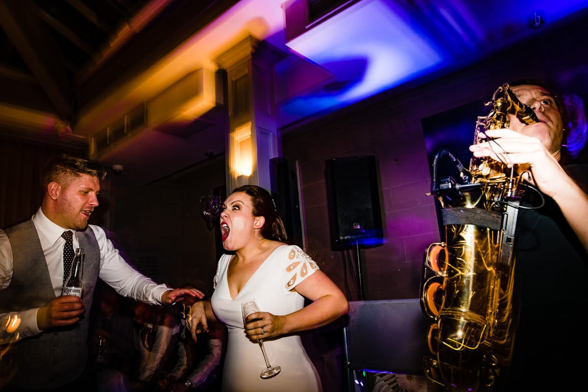 bride gets excited by wedding music on dance floor candid