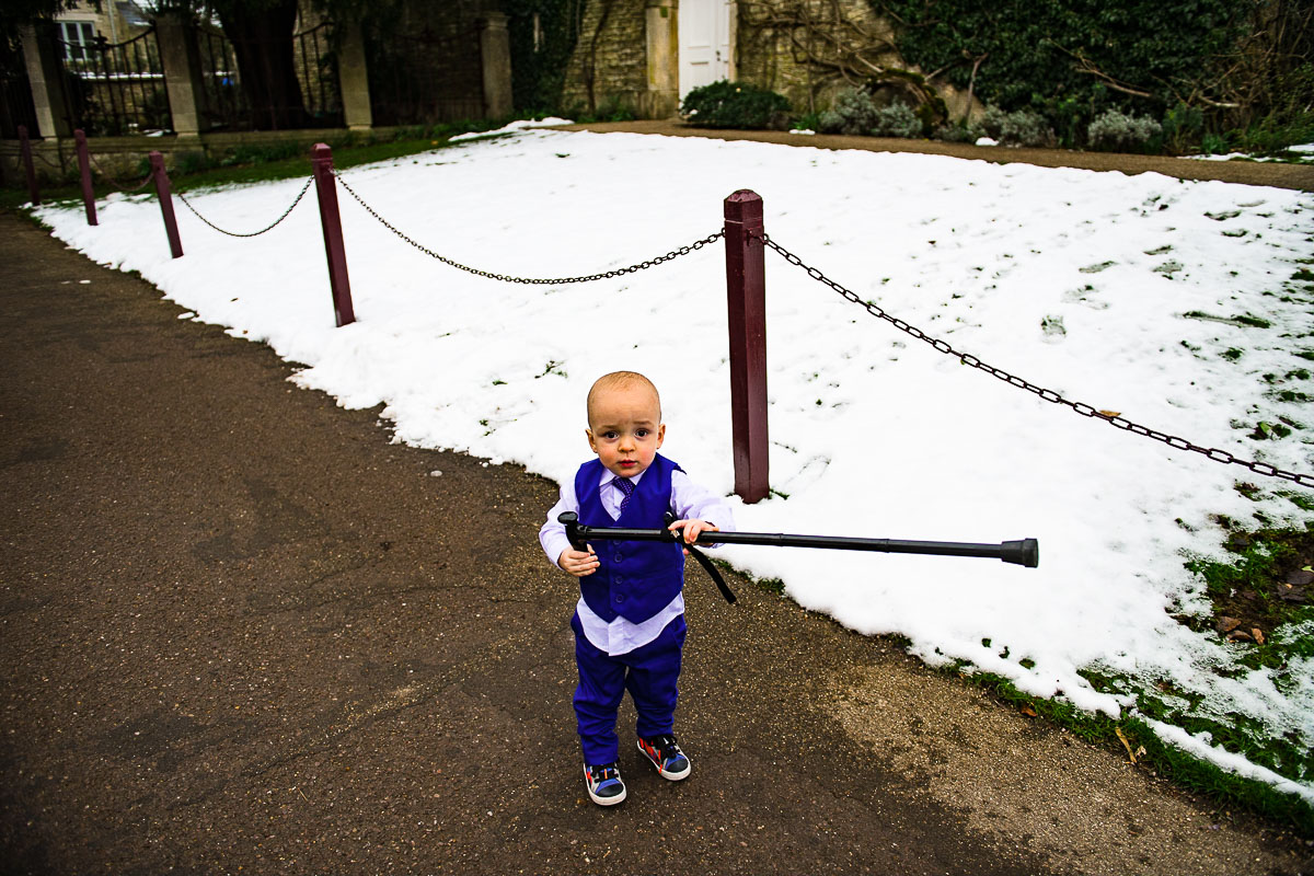 Pageboy picks up walking stick in the snow