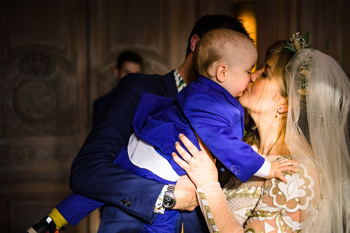 bride kisses her baby son Cowley manor Gloucestershire wedding venue
