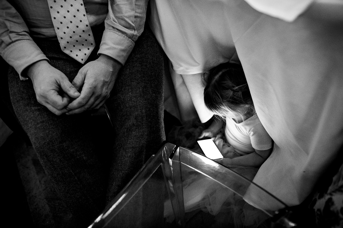 young girl under table on phone wedding candid photo