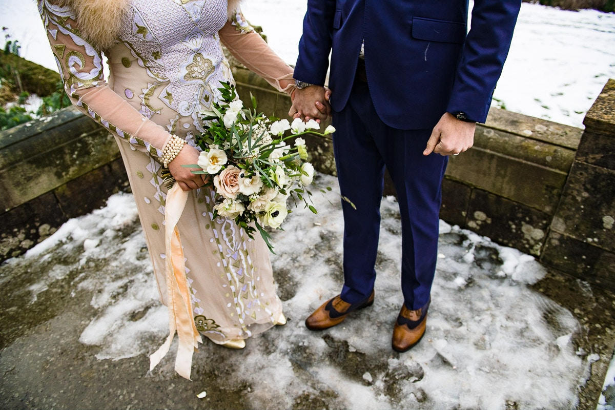 bride and groom hold hands and bouquet snow winter wedding detail