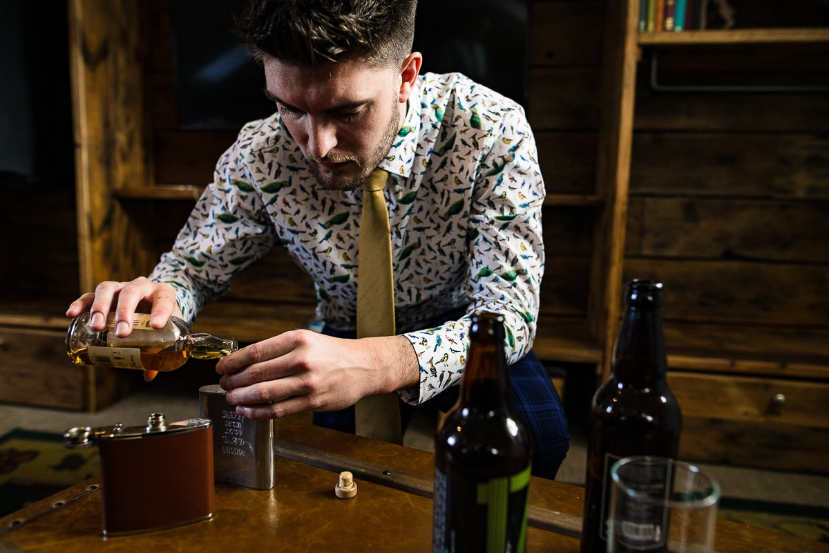 wedding usher pours whiskey into hip flask