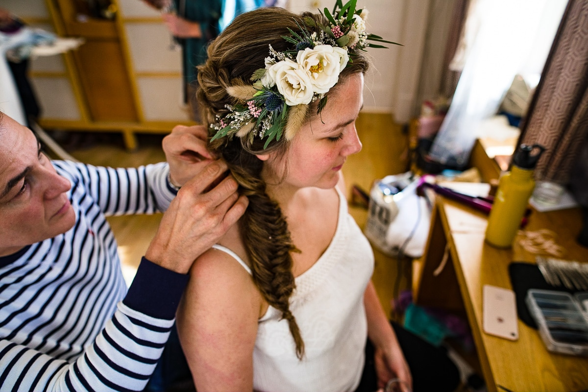 hairstylist adjusts flower crown by Flowers by Passion