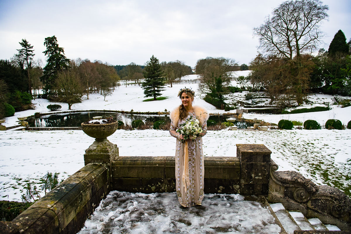 Cotswold bride in snow with winter bouquet Cowley Manor wedding photos