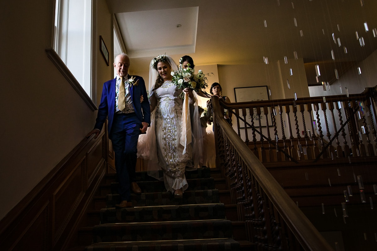 bride staircase window light Cowley Manor wedding photos