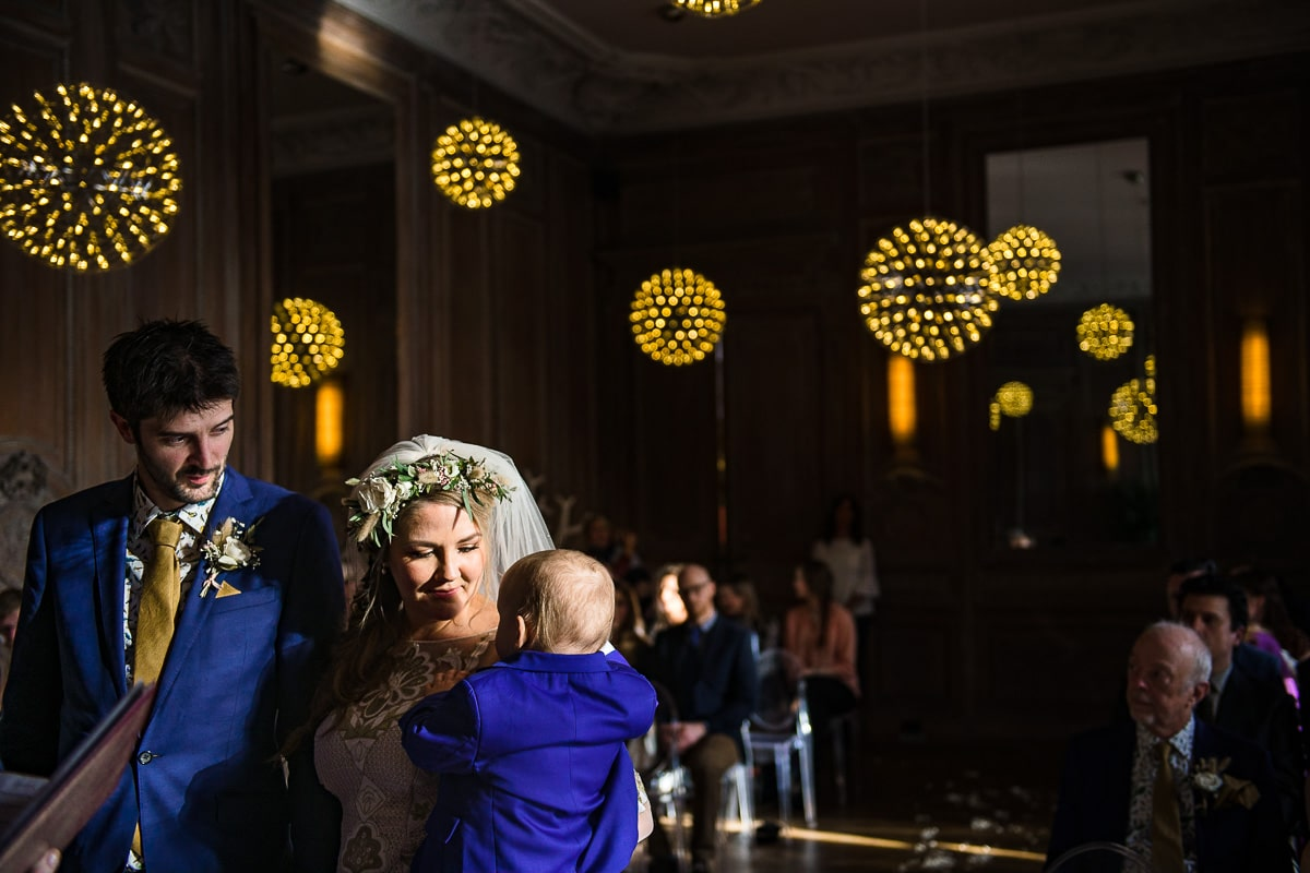 bride and groom with baby wedding ceremony Cowley manor