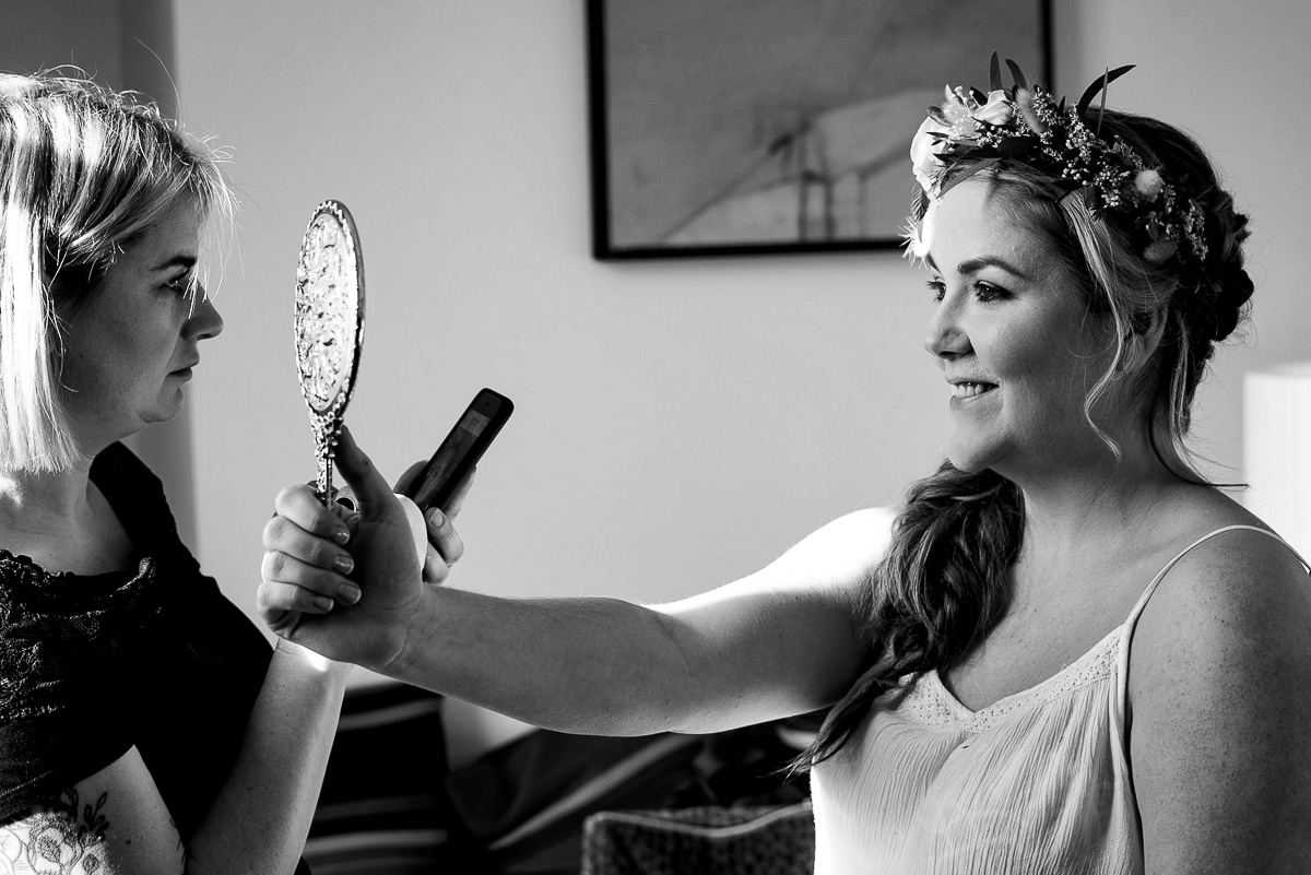 bride admires her makeup in mirror flower crown