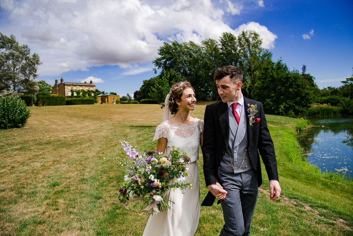 bride and groom stroll through field in countryside