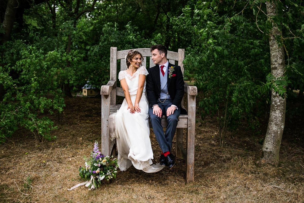 bride and groom sit and pose on tall chair in garden