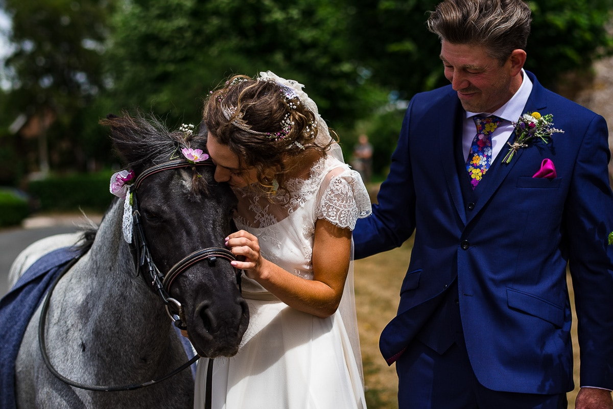 bride embraces decorated horse while father watches