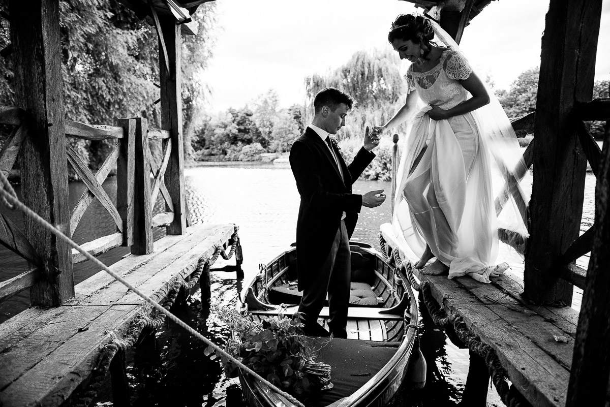 groom helps wife into small wedding boat