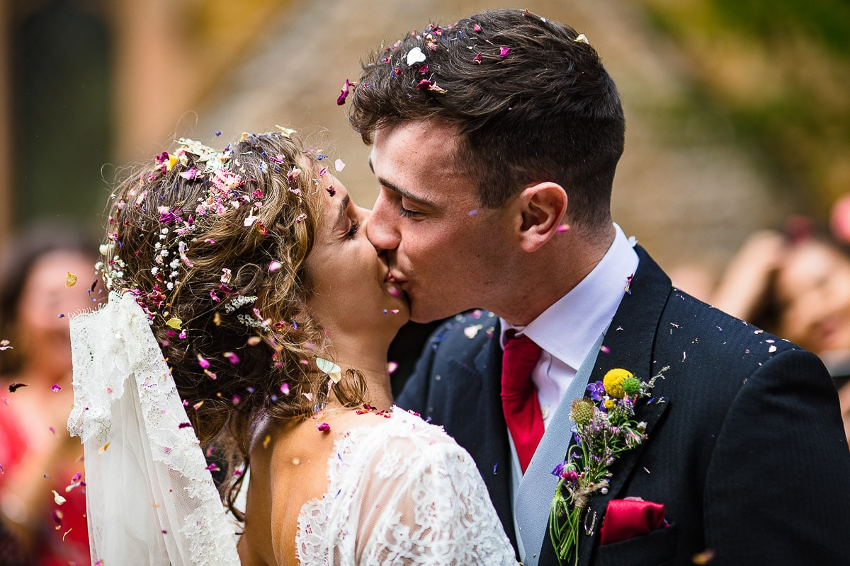 bride and groom kiss as guests celebrate with flower buds