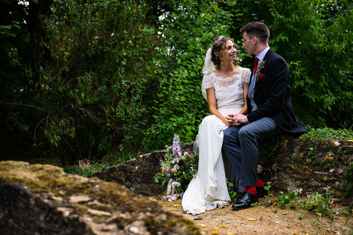 bride and groom sit on fern bridge in marquee garden
