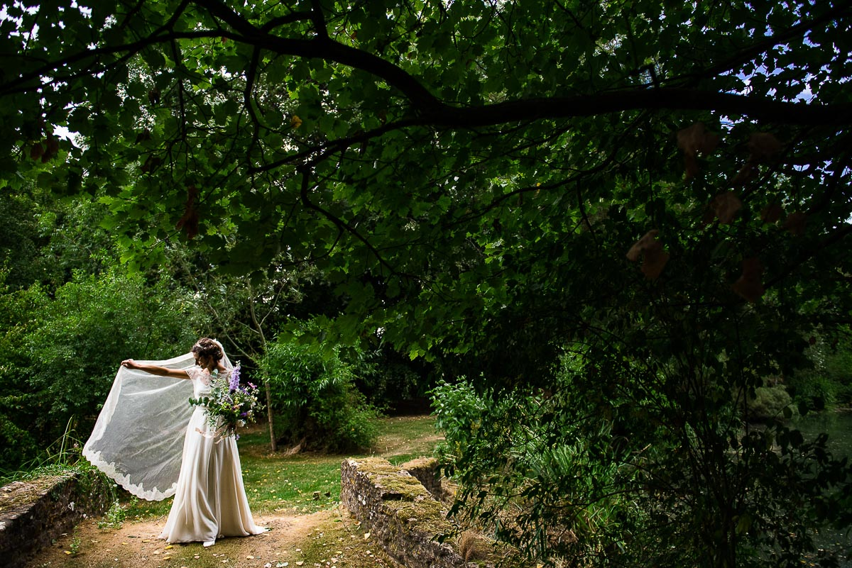 bride poses with veil in country garden