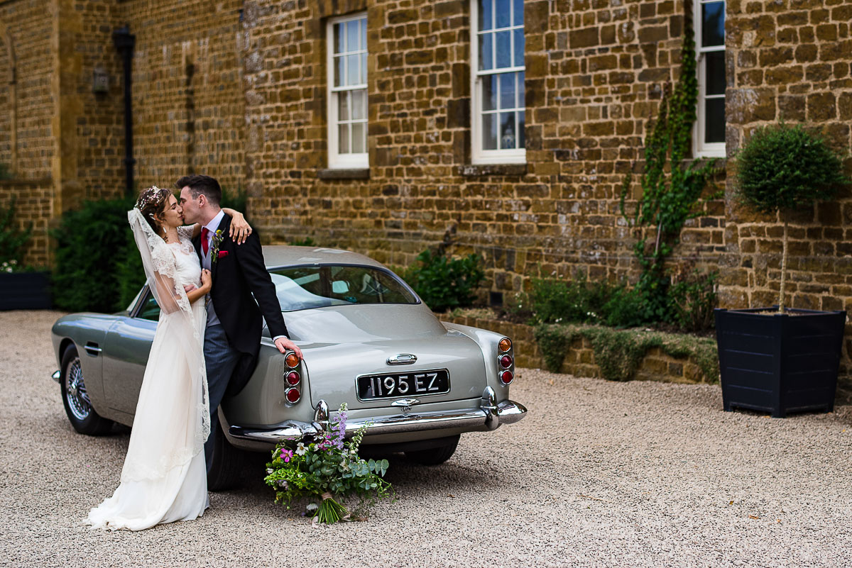 bride and groom embrace and kiss against vintage car
