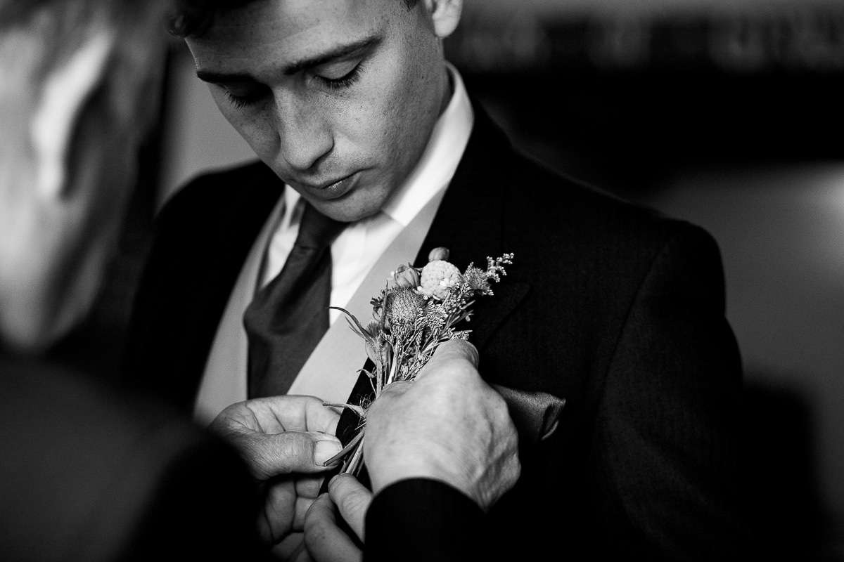 groom watches as best man adjusts his corsage