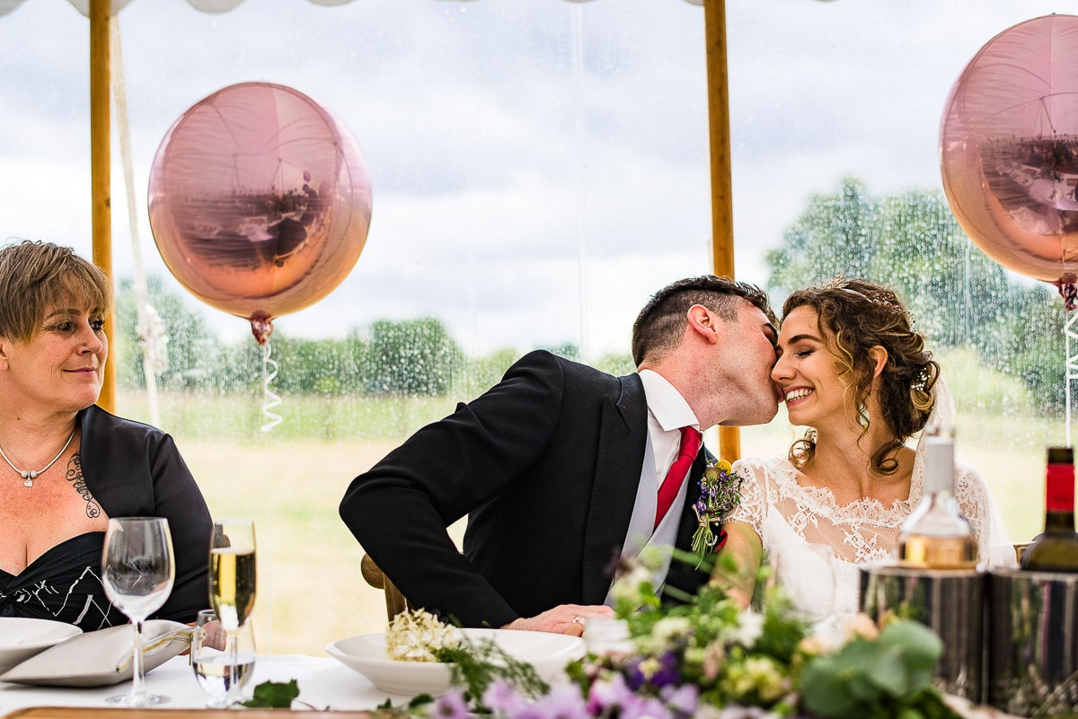 groom kisses bride at buffet table during dinner