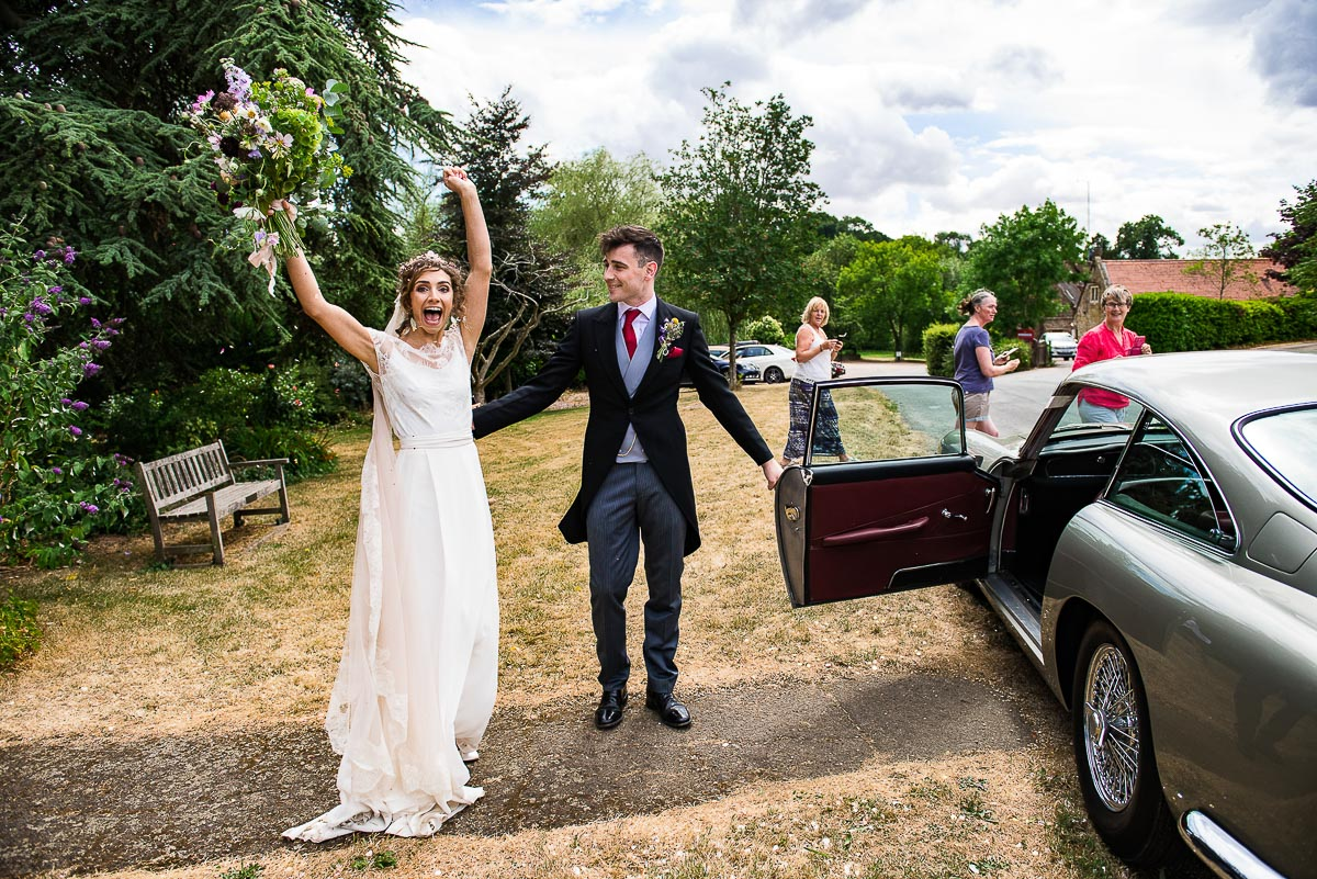 bride celebrates as she exits her her vintage car and arrives at countryside marquee