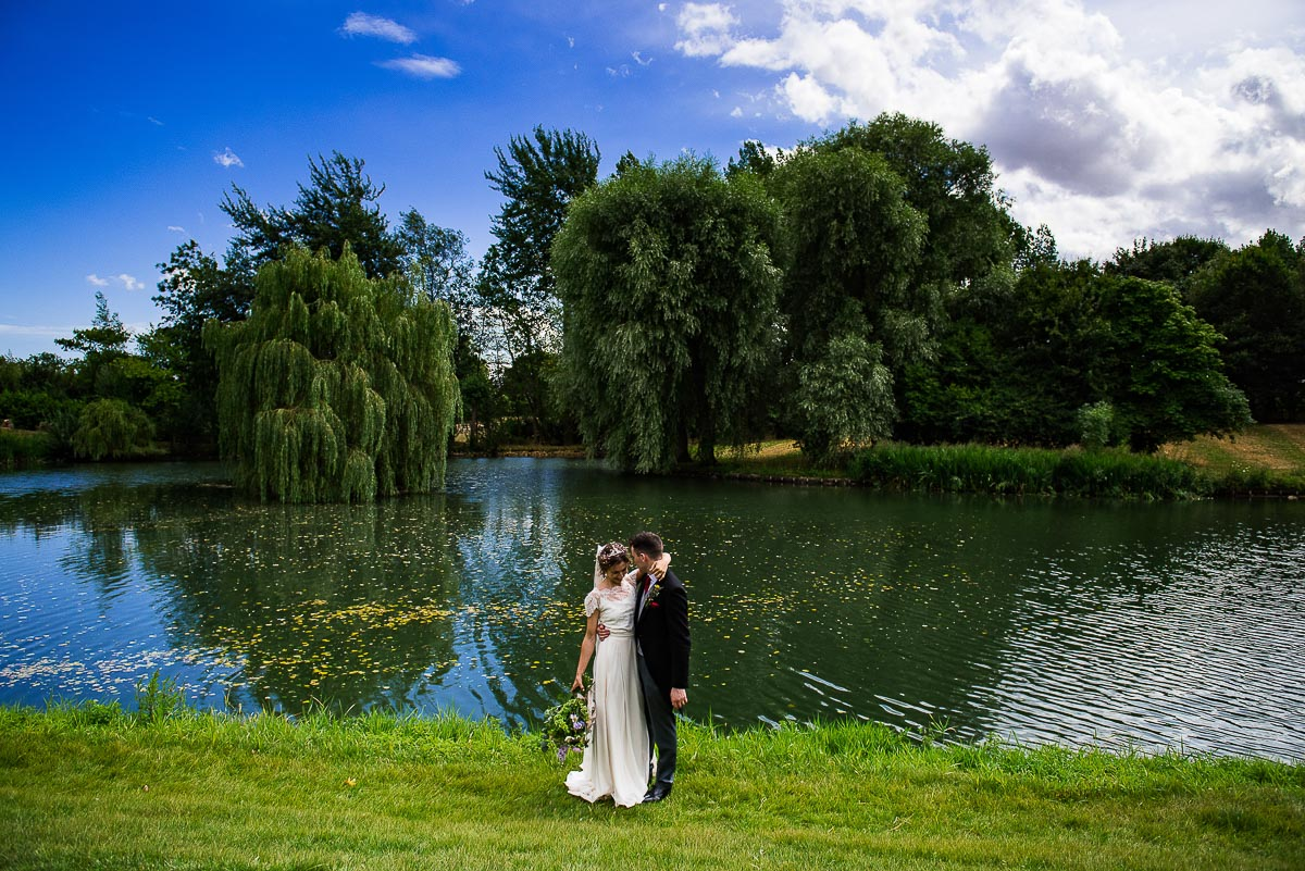 bride and groom embrace by enchanting pond and willow trees