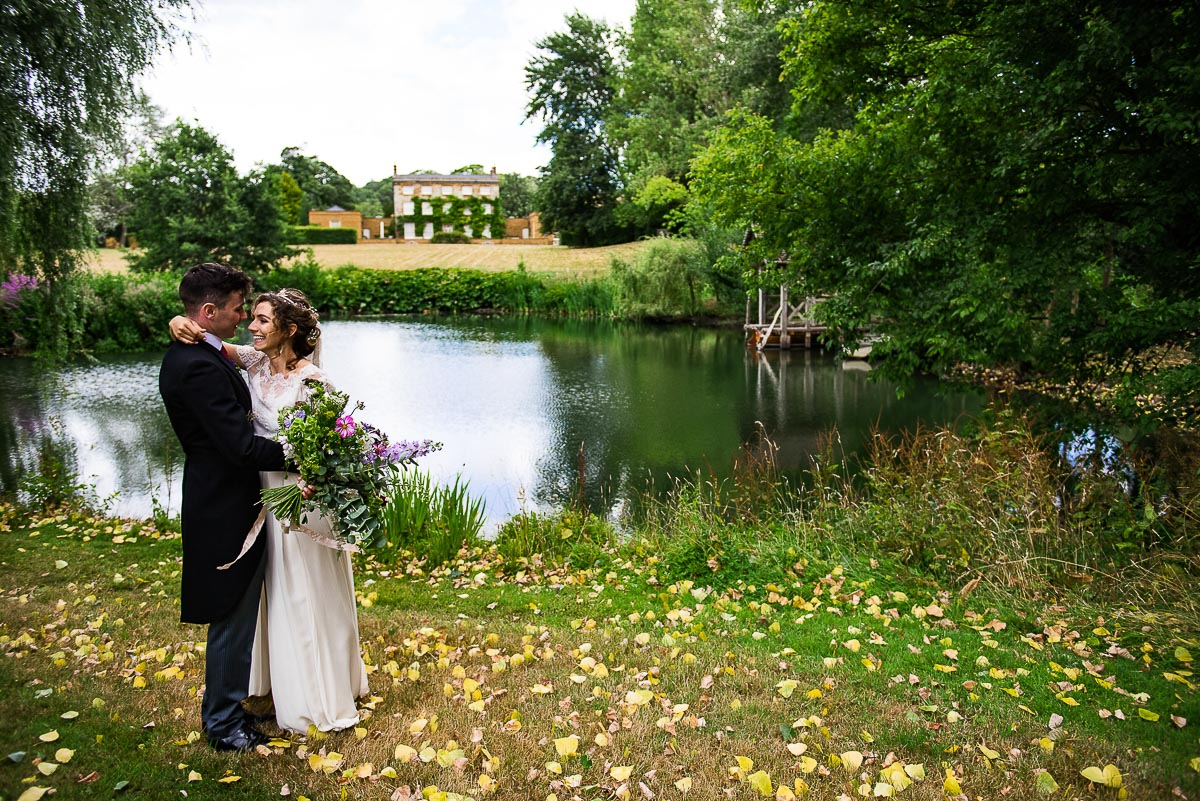 bride and groom take a stroll by countryside pond