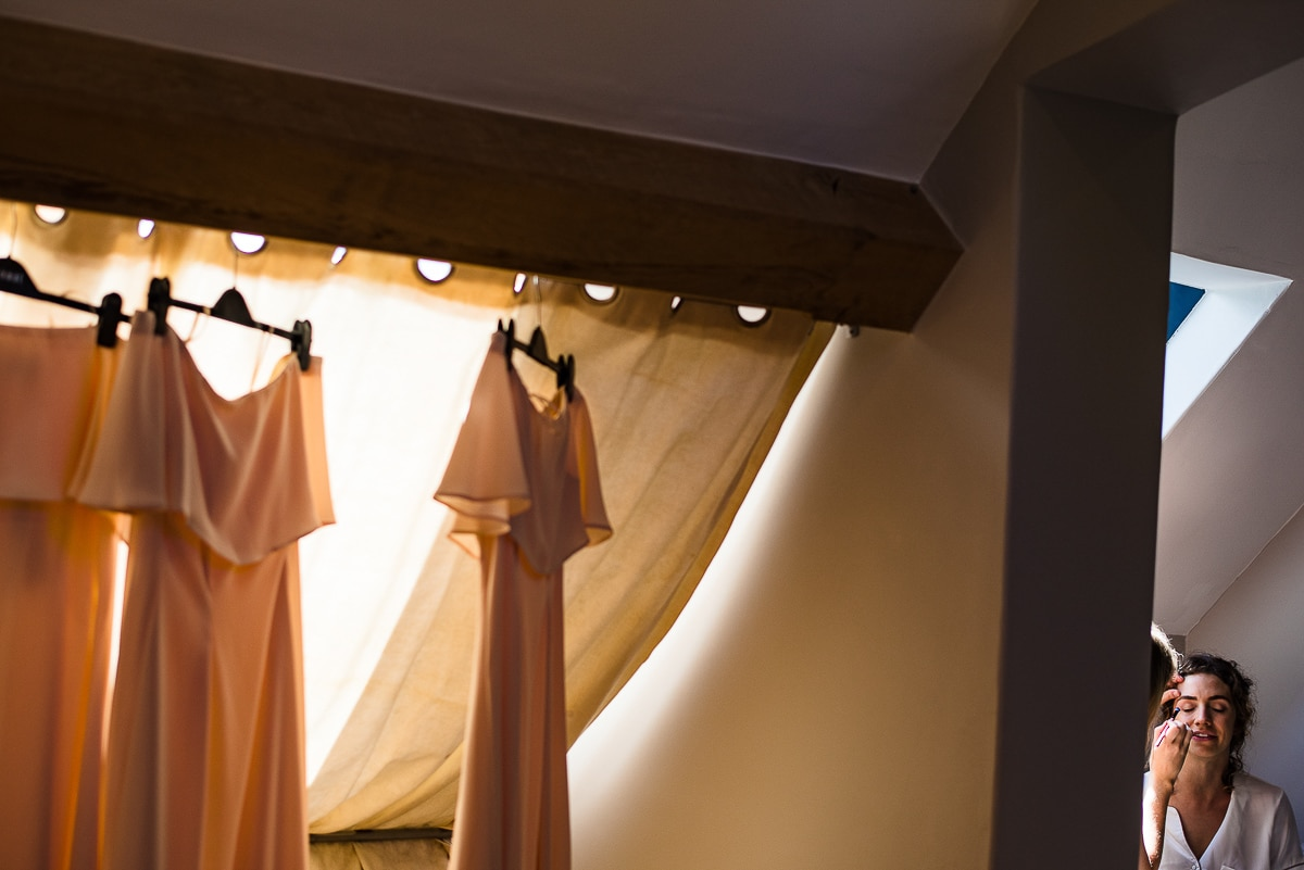 bridesmaids dresses hung on window and preparation for wedding detail