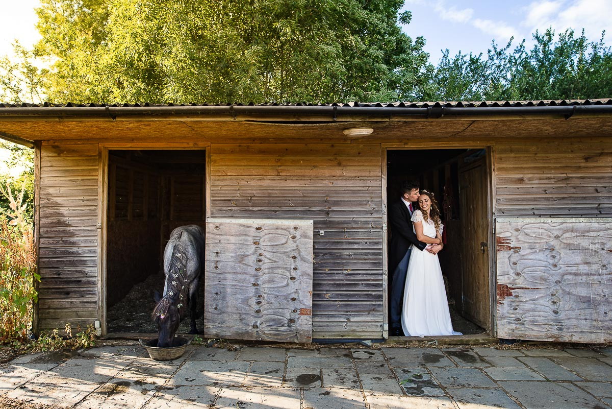 bride and groom pose in stable in countryside garden