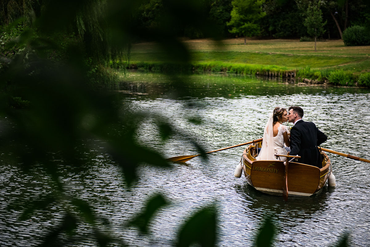 bride and groom kiss while rowing small boat across lake