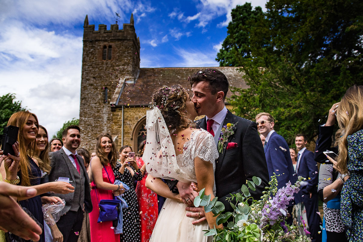 bride and groom kiss as guests celebrate with flower confetti