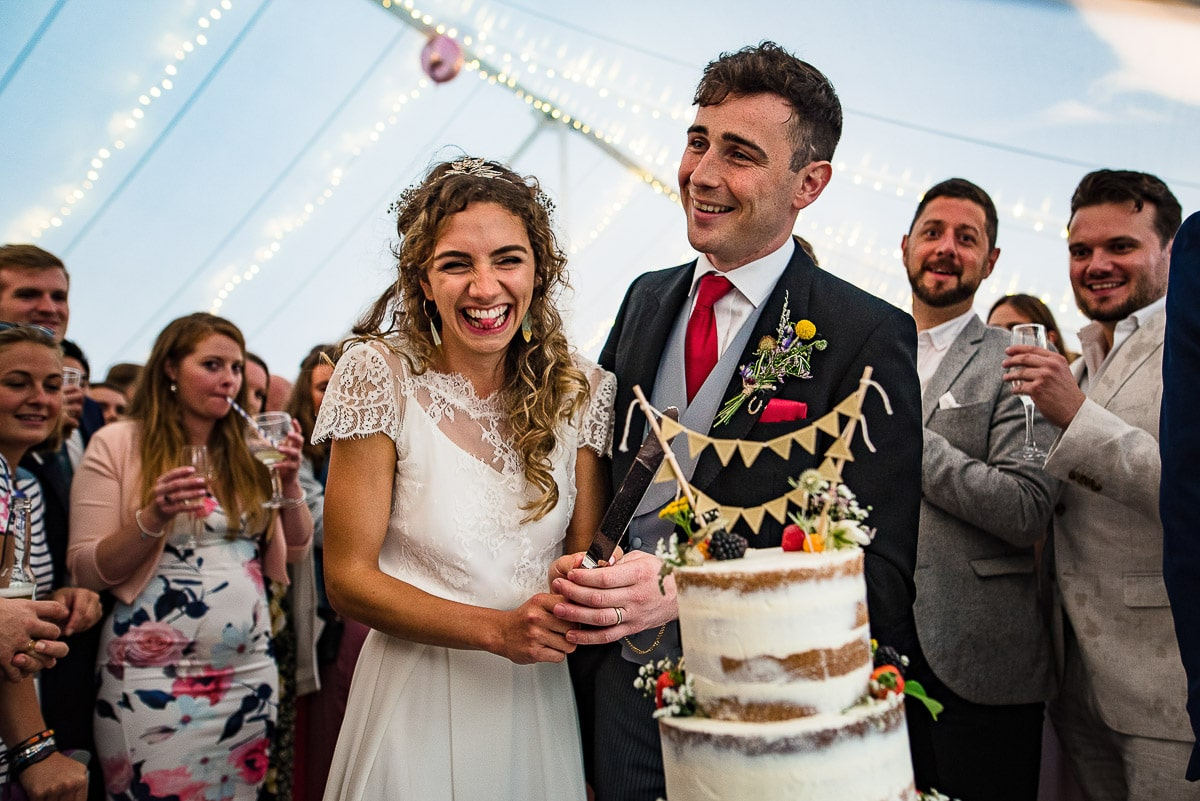 guests watch as bride and groom slice into wedding cake
