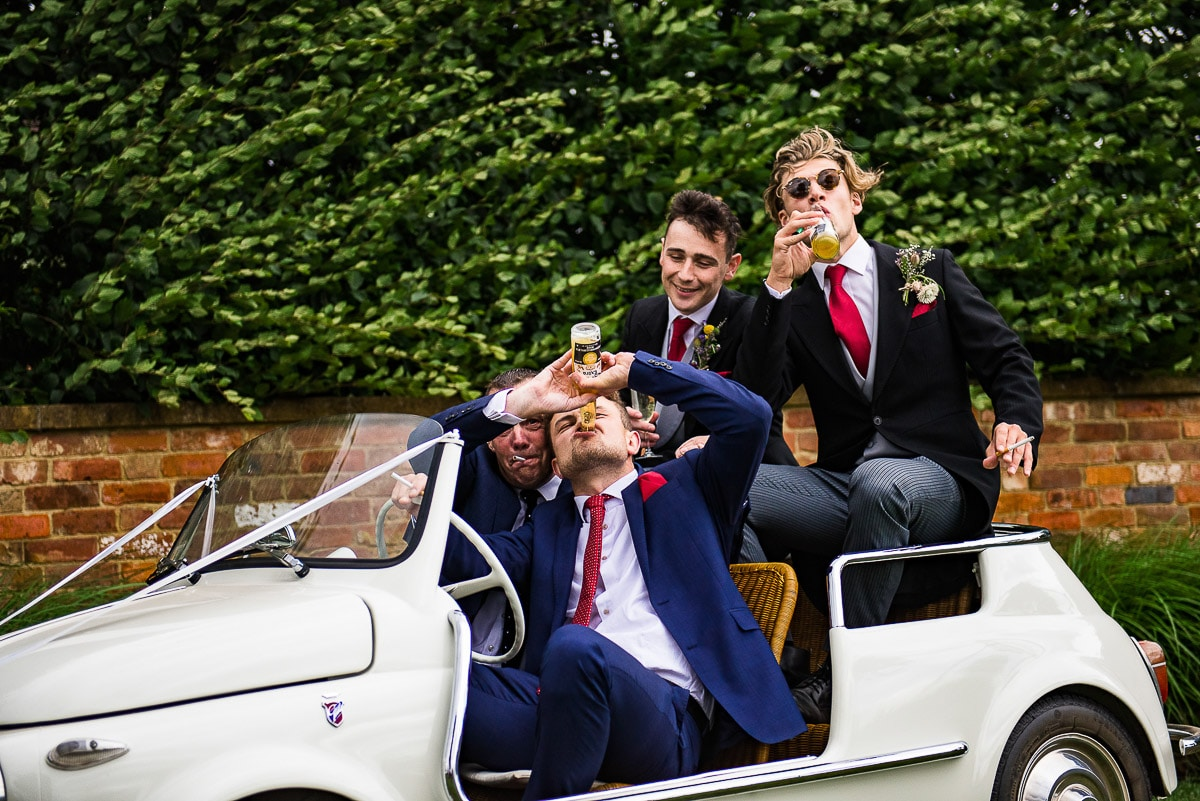 groomsmen and groom enjoy a drink as they pose in car