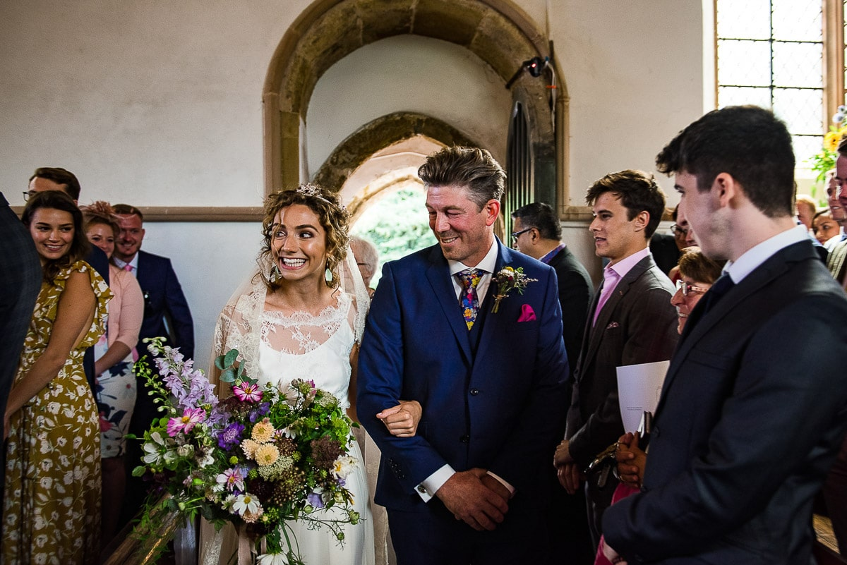 bride grins as father walks her down the aisle