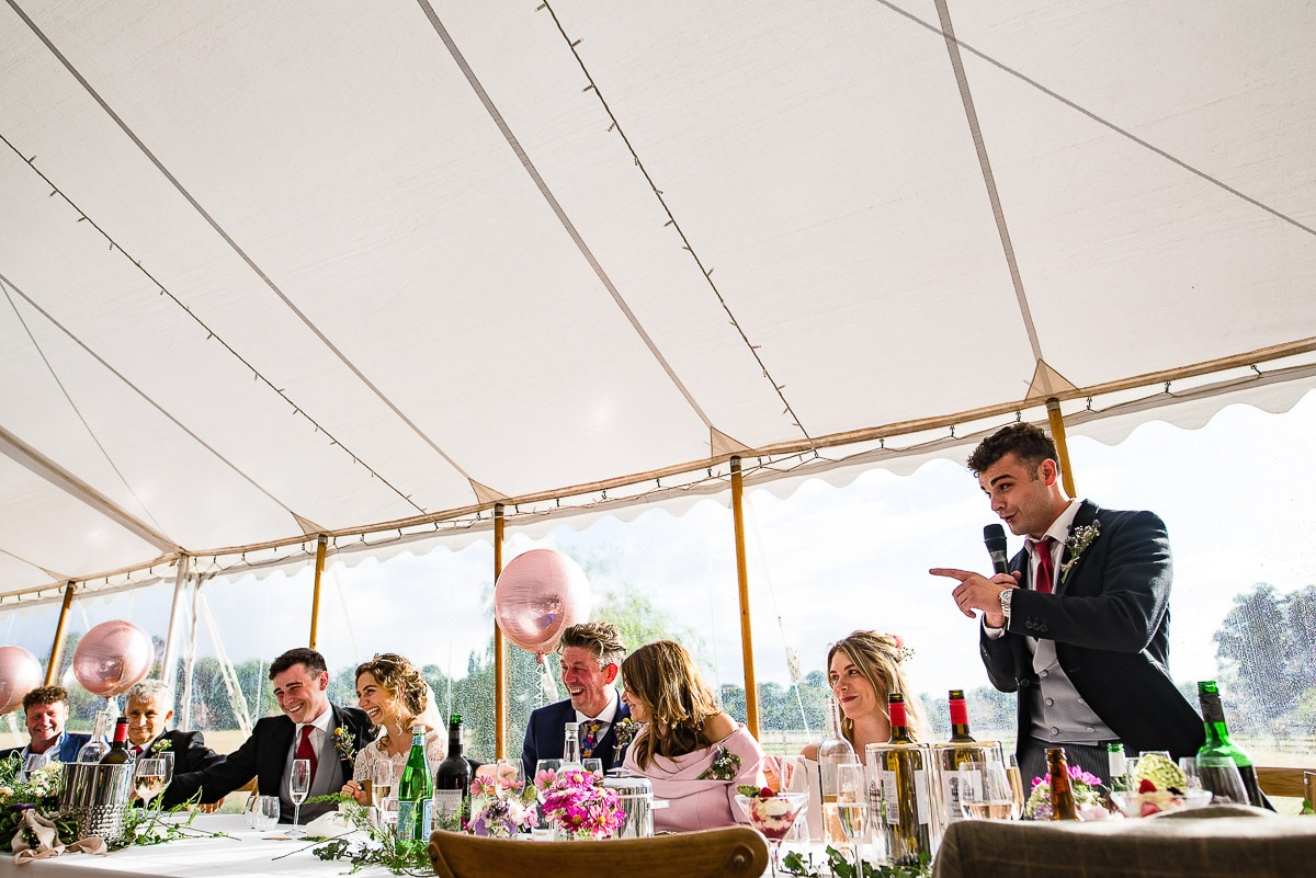 groomsman makes wedding speech as guests laugh