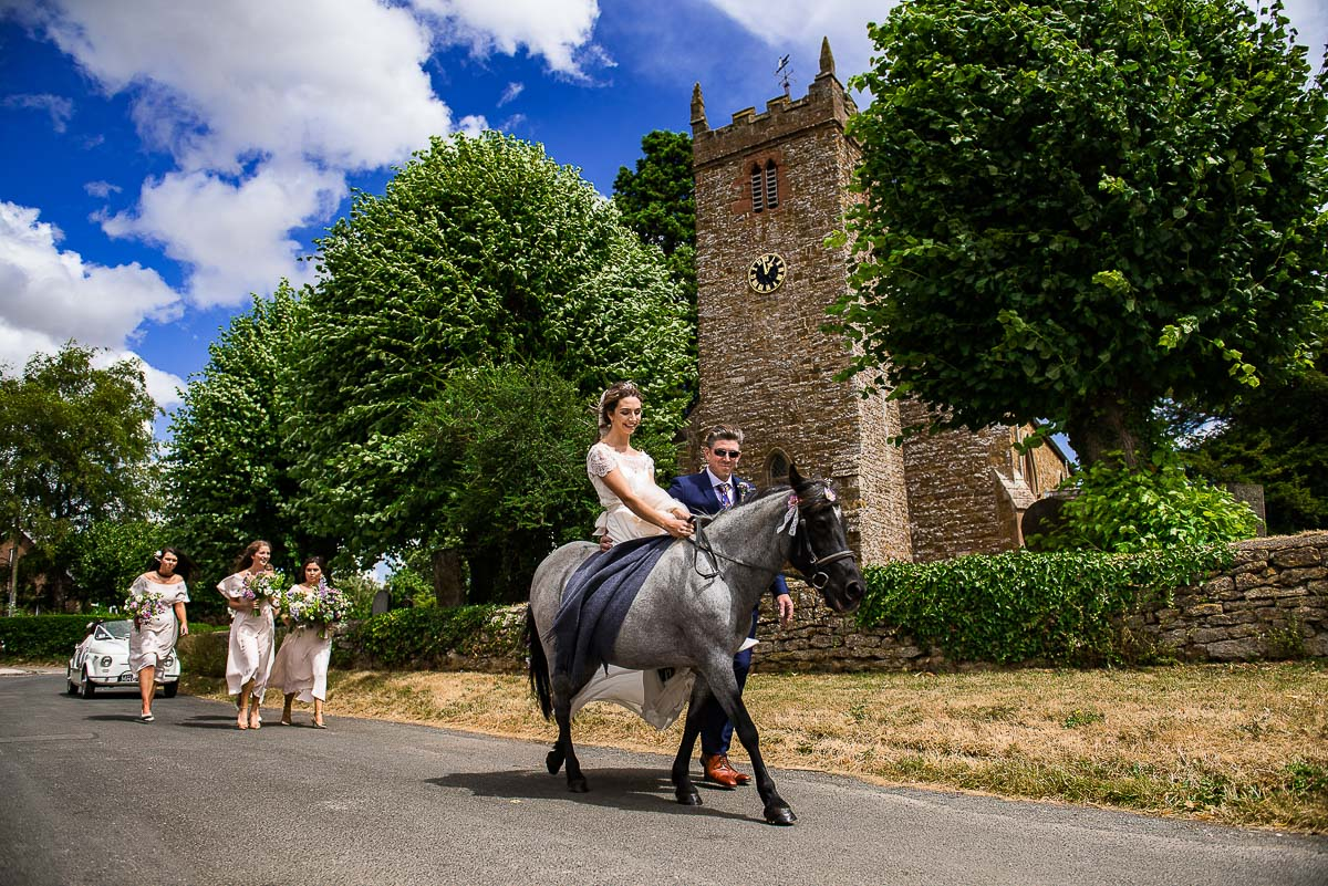 father guides bride as she arrives to wedding on horse
