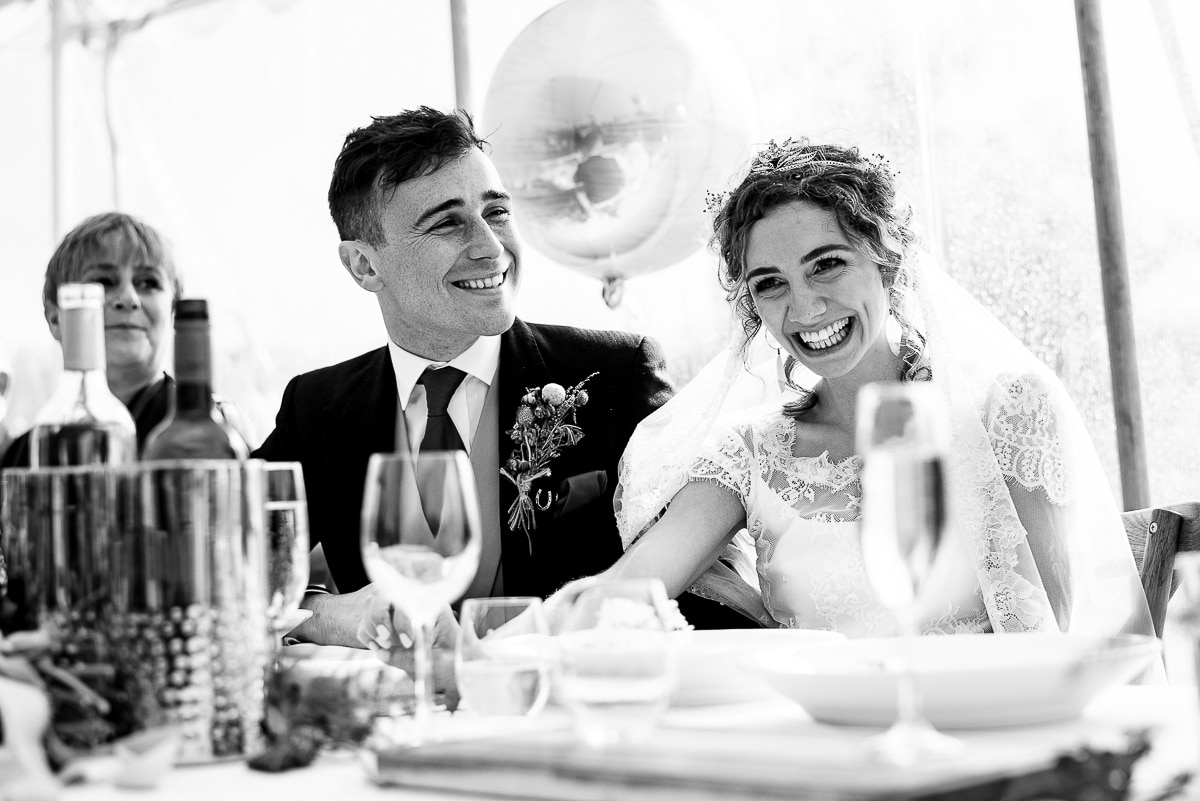 bride and groom laugh at wedding speech at dinner table