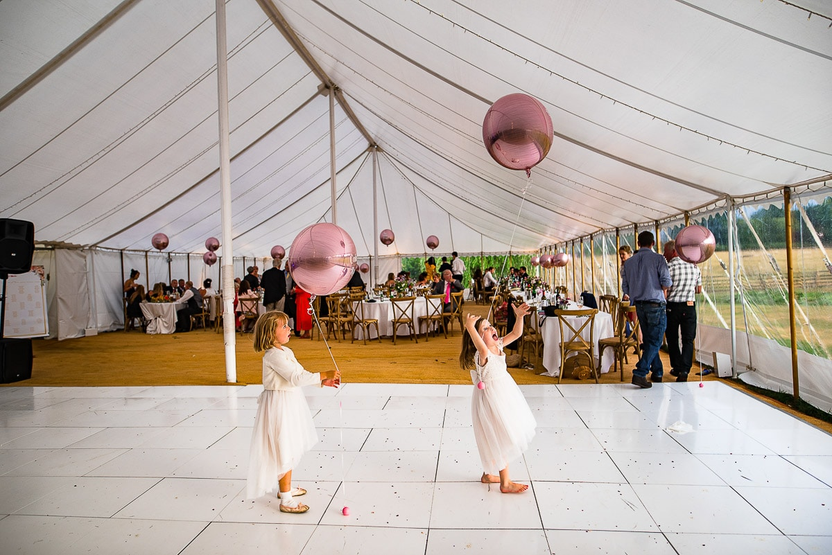 young wedding guests play with balloons at marquee wedding