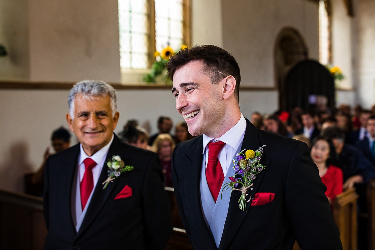 groom smiles nervously as he waits for bride at alter