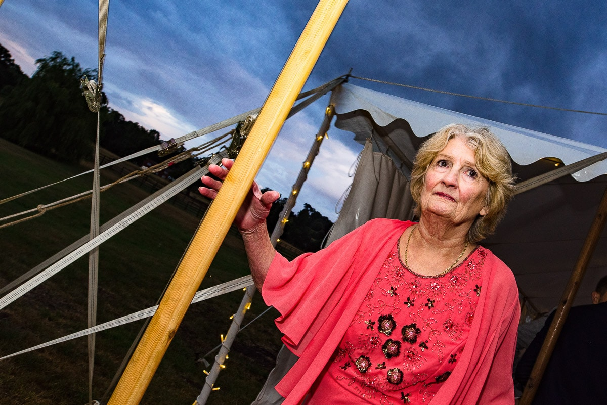 wedding guest looks worried as she holds onto tent post