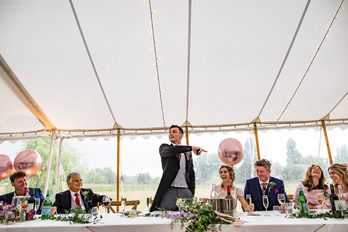 groom points and makes jokes as he makes wedding speech