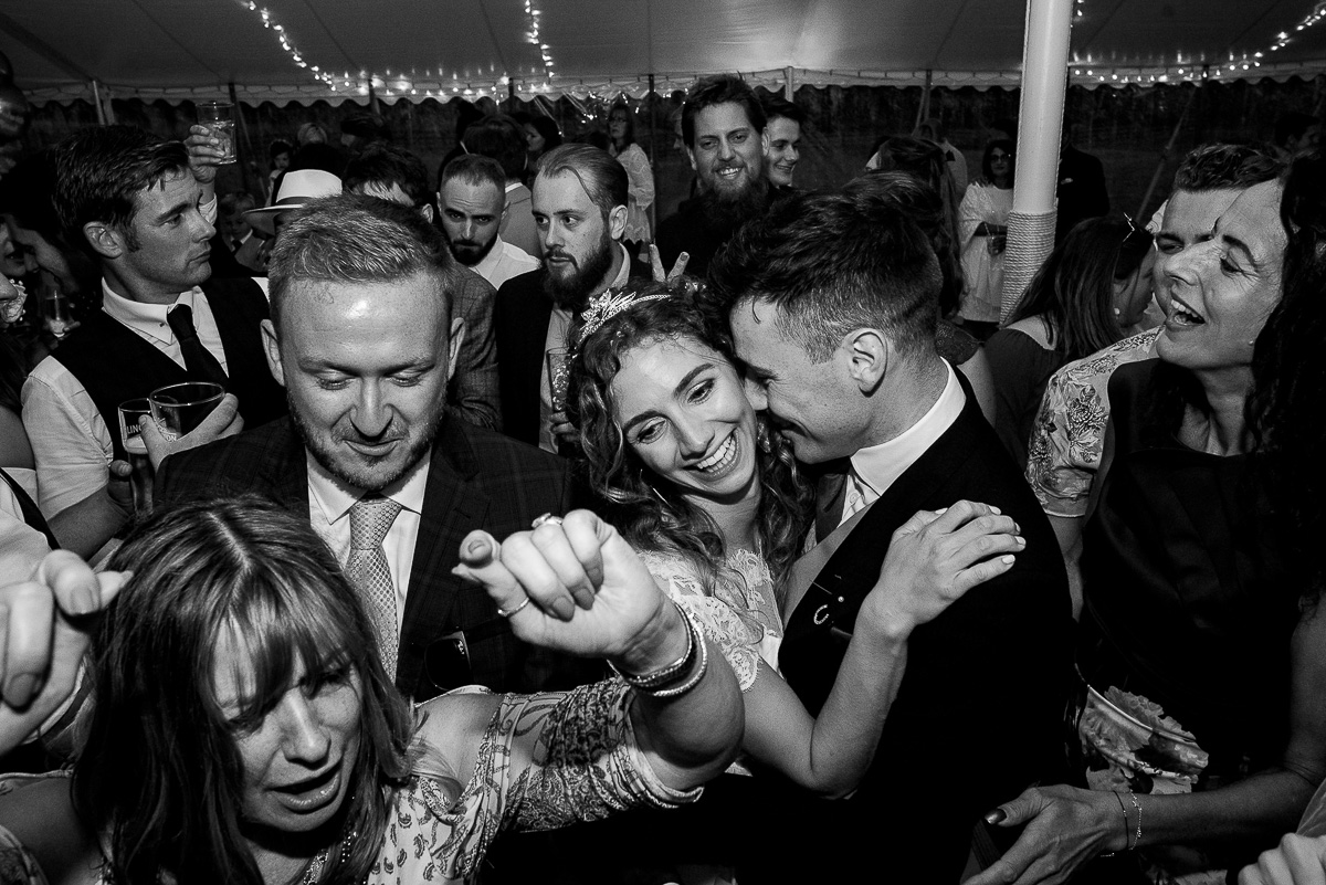 bride and groom embrace on busy dance floor